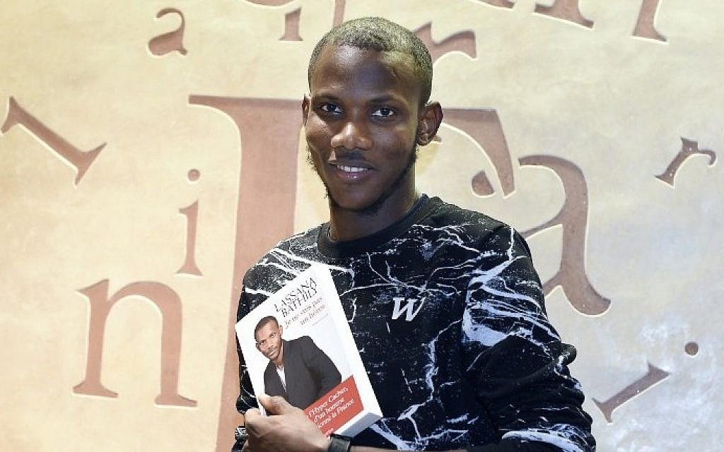 """Lassana Bathily, the employee of the Hyper Cacher supermarket in Paris who helped shoppers hide from an Islamist gunman who attacked the store on January 9, 2015, posing with his book """"Je ne suis pas un heros"""" (I Am Not A Hero), December 16, 2015. (AFP/Dominique Faget)"""