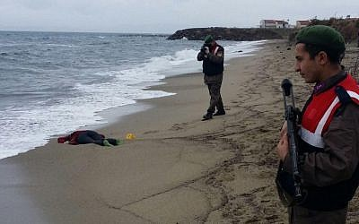 Turkish soldiers take photos of the body of a migrant washed up ashore in Izmir's Dikili district on January 5, 2016. (AFP/Dogan News Agency/Taylan Yildirim/Turkey OUT)