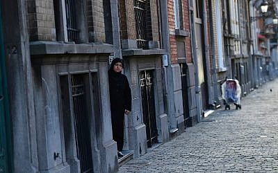 A woman stepping out of an apartment building in the Brussels district of Schaerbeek, January 8, 2016. Belgian police have found three belts for possible use in suicide attacks, traces of explosives, and a fingerprint of wanted Paris attacks suspect Salah Abdeslam at the site, prosecutors said. (AFP/Emmanuel Dunand)