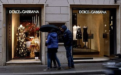 People stand in front of a Dolce e Gabana shop window in downtown Rome's Via Condotti, January 8, 2016. (AFP/FILIPPO MONTEFORTE)