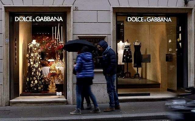 0e845277e1ce People stand in front of a Dolce e Gabana shop window in downtown Rome s  Via Condotti