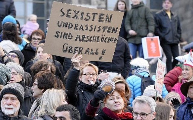 "A woman holds up a sign reading ""Sexists and racists are assholes-everywhere"" while taking part in a demonstration against violence against women in front of the cathedral in Cologne, western Germany, on January 9, 2015 (Roberto Pfeil/AFP)"