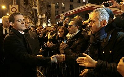 Manuel Valls (L) shakes hands with people on January 9, 2016 near the Hyper Cacher, a kosher supermarket, during a ceremony to pay tribute to the victims of the attack on the supermarket on January 9, 2015. (Jacques Demarthon/Pool/AFP)