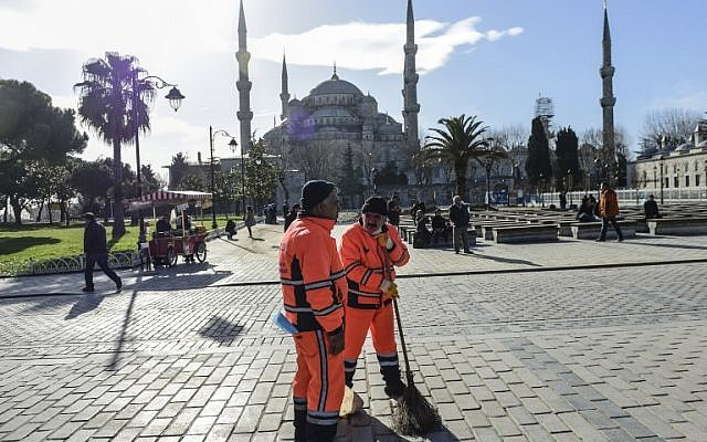 Municipal workers clean outside the Blue Mosque near the site of a blast in Istanbul's tourist hub of Sultanahmet on January 12, 2016. (AFP/BULENT KILIC)