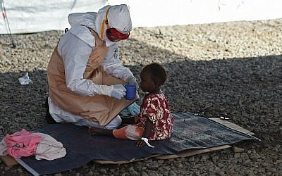 This file photo taken on November 15, 2014 shows a health worker wearing protective equipment giving a drink to a young Ebola patient at Kenama treatment center run by the Red Cross in Sierra Leone. (Francisco Leong/AFP)