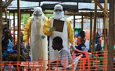 This file photo taken on August 15, 2014 shows a Doctors Without Borders (MSF) medical worker wearing protective clothing while speaking to a colleague at an MSF facility in Kailahun, Sierra Leone. (Carl de Souza/AFP)