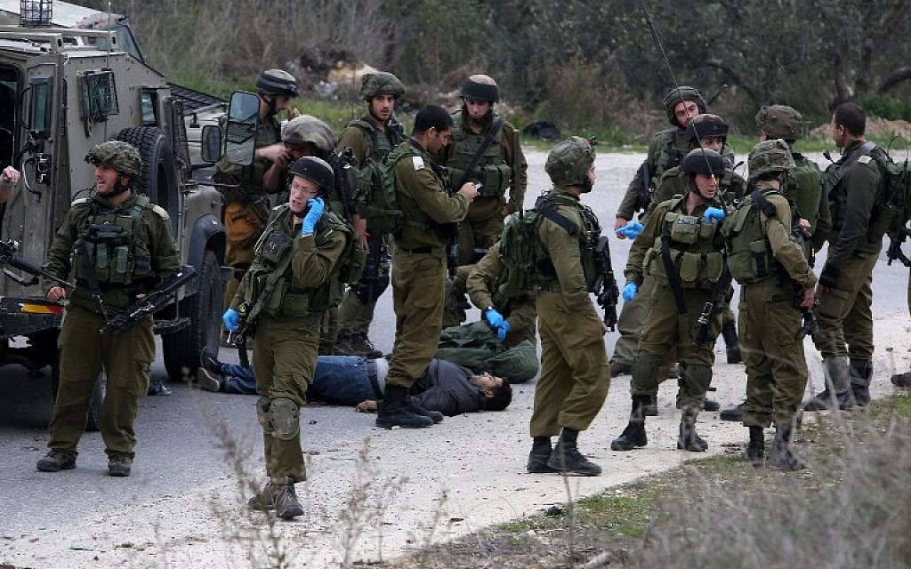 Israeli security forces gather around the body of a Palestinian man killed during a stabbing attack in the village of Assira al-Shamaliya near Nablus, in the West Bank, on January 14, 2016.  (AFP/JAAFAR ASHTIYEH)