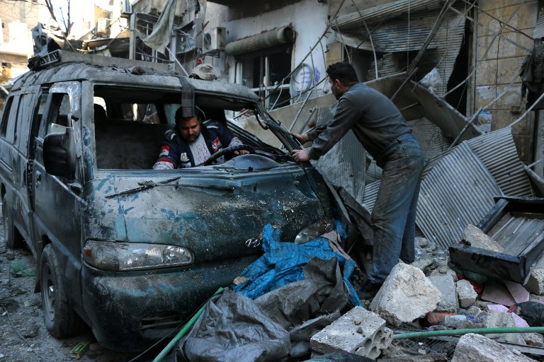 Syrian men inspect a damaged vehicle in the rubble following a reported air strike by Syrian government forces on the Sukkari neighbourhood of Syria's northern city of Aleppo, on January 16, 2016. (AFP/Karam Al-Masri)