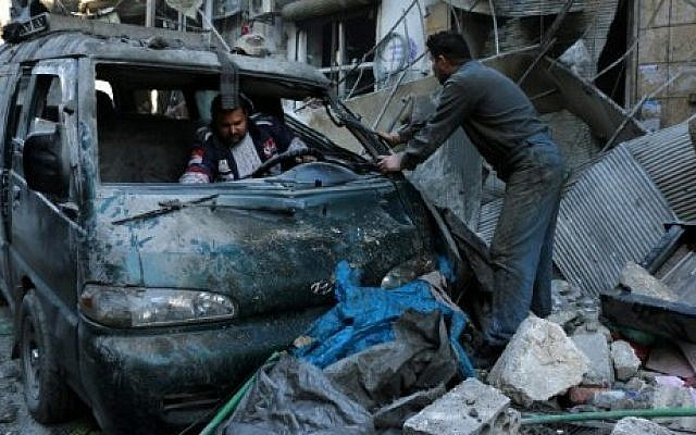Syrian men inspect a damaged vehicle in the rubble following a reported air strike by Syrian government forces on the Sukkari neighborhood of Syria's northern city of Aleppo, on January 16, 2016. (AFP/Karam Al-Masri)