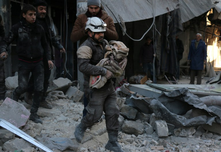 A Syrian Civil Defence worker carries a child wrapped in a blanket over the rubble following a reported air strike by Syrian government forces on the Sukkari neighborhood of Syria's northern city of Aleppo, on January 16, 2016. (AFP/Karam Al-Masri)