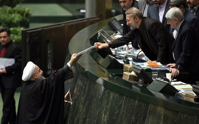 Iranian President Hassan Rouhani, left, presents the proposed annual budget to Parliament Speaker Ali Larijani Ali Larijani in the capital Tehran, on January 17, 2016, after sanctions were lifted under Tehran's nuclear deal with world powers. (AFP/Atta Kenare)