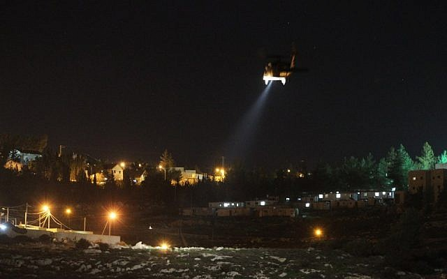 A picture taken from the Palestinian village of Dahriya shows an Israeli army helicopter flying over the Otniel settlement in the southern West Bank as security forces search for a Palestinian suspected of stabbing to death Dafna Meir at her home on January 17, 2016. (AFP/Hazem Bader)