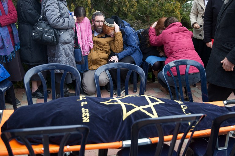 The husband and children (C) of stabbing attack victim Dafna Meir mourn in front of her wrapped body during her funeral ceremony in the settlement of Otniel in the southern West Bank on January 18, 2016 (AFP / MENAHEM KAHANA)