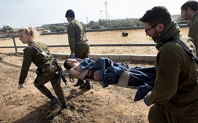 An injured Palestinian teen suspected of stabbing a woman in the settlement of Tekoa is evacuated on a stretcher by IDF medics on Monday, January 18, 2016 (AFP/MENAHEM KAHANA)