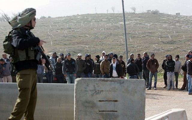 An Israeli soldier stands guard next to Palestinian workers who were transported out of the Tekoa settlement south of Jerusalem following a terror attack in the community on January 18, 2016. (AFP / MENAHEM KAHANA)