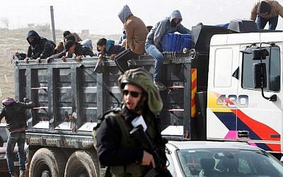 Palestinian workers being transported out of the Tekoa settlement south of Jerusalem on January 18, 2016 following a stabbing attack. AFP / MENAHEM KAHANA)