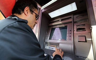 An Iranian man withdraws money from an ATM machine at a Bank Sepah in the capital Tehran on January 19, 2016. (AFP/Atta Kenare)