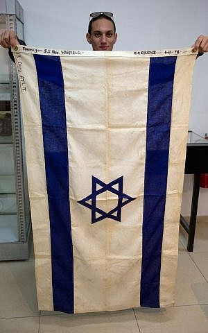 A file photo shows an employee of the Kedem Auction House in Jerusalem showing the flag of the iconic ship the SS Exodus, November 15, 2015. (AFP/MENAHEM KAHANA)