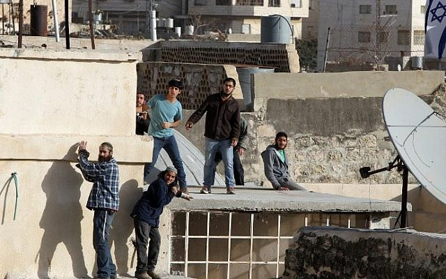 Jewish settlers stand on the roof of a building after entering two homes in the center of Hebron on January 21, 2016. (AFP/Hazem Bader)