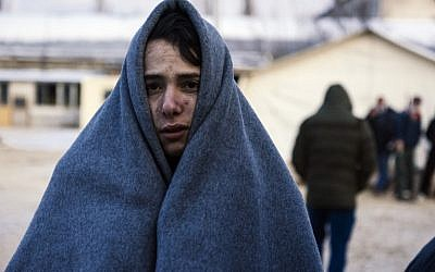 A migrant wrapped in a blanket to keep warm waits at a registration camp in southern Serbian town of Presevo on January 22, 2016, after crossing the Macedonian border. (AFP / DIMITAR DILKOFF)