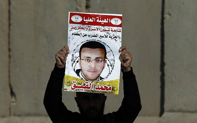 Photo taken on January 22, 2016, shows a Palestinian man carrying a placard bearing a portrait of Palestinian journalist Mohammed al-Qiq during a demonstration near Ramallah demanding his release from an Israeli jail. (Abbas Momani/AFP, File)