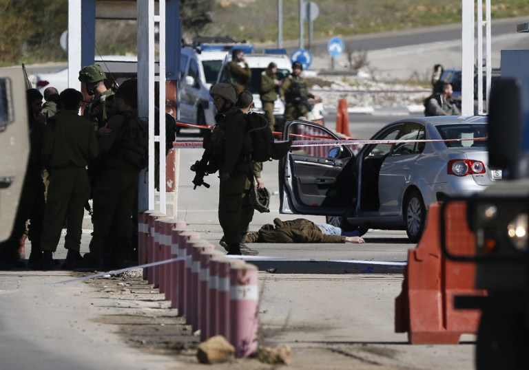 Israeli security forces at the scene of a shooting attack at a checkpoint near the Beit El settlement in the West Bank on Sunday, January 31, 2016 (AFP / ABBAS MOMANI)