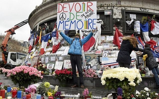 """Jean-Baptiste Redde aka Voltuan holds up a banner that reads, """"We must remember"""" following a remembrance rally attended by the President of France at Place de la Republique on January 10, 2016 in Paris, France (AFP PHOTO / DOMINIQUE FAGET)"""