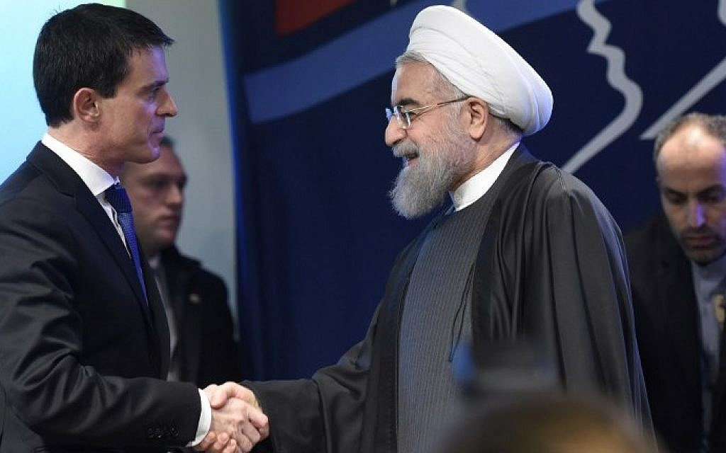 French Prime Minister Manuel Valls (L) shakes hands with Iranian President Hassan Rouhani on January 28, 2016 during a meeting at the  French employers association MEDEF headquarters in Paris. (AFP/ERIC FEFERBERG)
