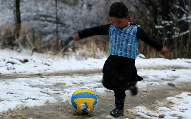 Afghan boy and Lionel Messi fan Murtaza Ahmadi, 5, wears a plastic bag jersey as he plays soccer in Jaghori district of Ghazni province on January 29, 2016. (AFP)