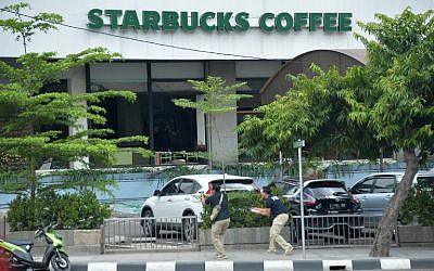 Plainclothes police aim their handguns towards suspects outside a cafe after a series of blasts hit the Indonesia capital Jakarta on January 14, 2016. (AFP PHOTO / Bay ISMOYO)