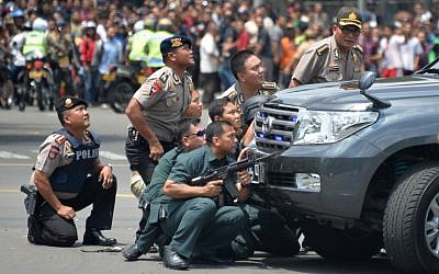 Indonesian police take position behind a vehicle as they pursue suspects after a series of blasts hit the Indonesia capital Jakarta on January 14, 2016. (AFP PHOTO / Bay ISMOYO)