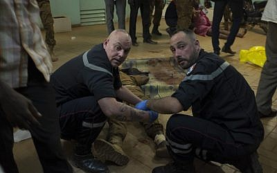 French first responders tend to wounded people in the surrounding of the Hotel Splendide and the Café Cappuccino during the attack on January 15, 2016.  (AFP PHOTO/NABILA EL HADAD)
