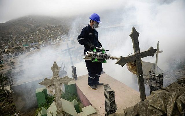 A specialist fumigates the Nueva Esperanza graveyard in the outskirts of Lima on January 15, 2016. Health officials fumigated the largest cemetery in Peru and second largest in the world to prevent Chikunguya and Zika virus, which affect several South American countries. AFP PHOTO/ERNESTO BENAVIDES / AFP / ERNESTO BENAVIDES