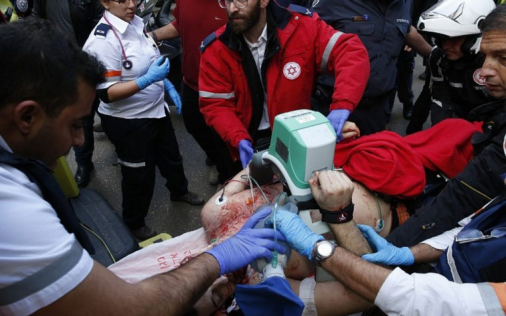 Medics give emergency treatment to a victim following an attack by an unidentified gunman in central Tel Aviv that killed two people and wounded seven others on January 1, 2016. (AFP PHOTO/JACK GUEZ)