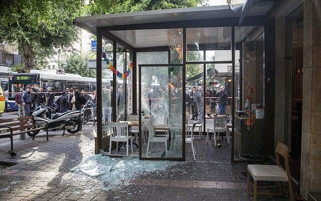 Israeli security forces and onlookers stand at the site an attack at a pub in Tel Aviv that killed two people on January 1, 2016. (AFP PHOTO/JACK GUEZ)