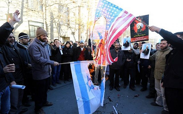 Iranian men burn Israeli and American flags during a demonstration against the execution of prominent Shiite Muslim cleric Nimr al-Nimr by Saudi authorities, on January 3, 2016, outside the Saudi embassy in Tehran. (AFP PHOTO / ATTA KENARE)