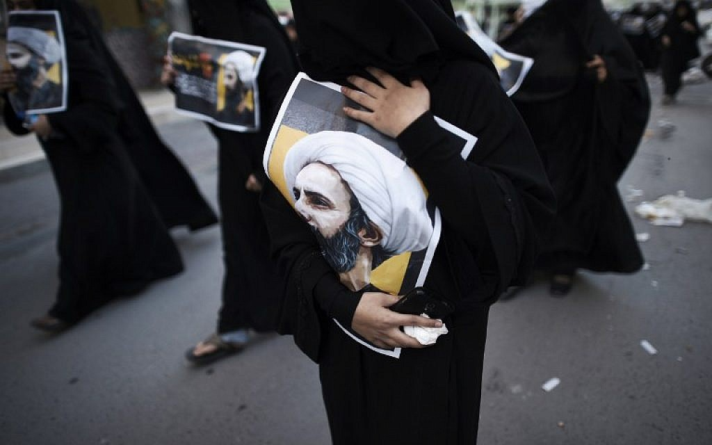 Bahraini women hold posters bearing portraits of prominent Shiite Muslim cleric Nimr al-Nimr during a protest against his execution by Saudi authorities, in the village of Jidhafs, west of the capital Manama on January 3, 2016. (Mohammed al-Shaikh/AFP)