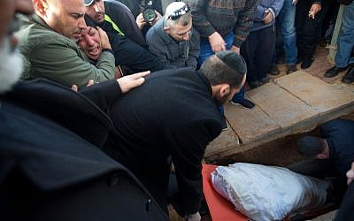 The family and friends of 30-year-old Tel Aviv shooting victim Shimon Ruimi, mourns as his body is lowered into the grave during his funeral in the southern town of Ofakim on January 3, 2016. (AFP PHOTO/MENAHEM KAHANA)
