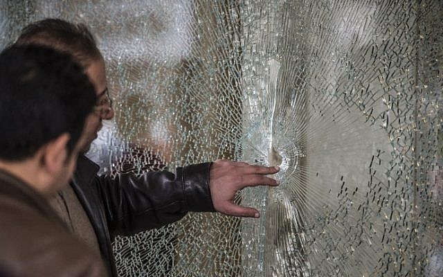 Egyptian forensic experts inspect a bullet-riddled window at the entrance of the Three Pyramids hotel in Cairo where Israeli tourists were shot at, January 7, 2016. (AFP Photo/ Khaled Desouki)
