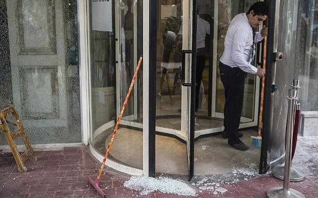 A Egyptian employee cleans up the entrance of the Three Pyramids hotel in Three Pyramids hotel in Cairo where Israeli tourists were shot at, January 7, 2016. (AFP Photo/ Khaled Desouki)