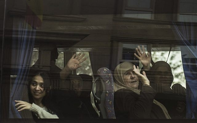 Israeli tourists wave from a bus as they leave the Three Pyramids hotel in Cairo's al-Harm district on January 7, 2016. (AFP Photo/ Khaled Desouki)