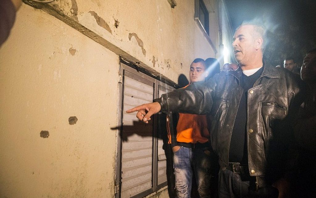 A man points out at bullet holes at the site where Israeli special forces shot Nashat Milhem, who murdered three people in a Tel Aviv shooting spree last week, in the  northern town of Arara, on January 8, 2016. (AFP PHOTO/JACK GUEZ)
