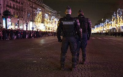 Police patrol ahead of New Year's celebrations on the Champs-Elysees, just before midnight in Paris on December 31, 2015. (AFP Photo/Florian David)