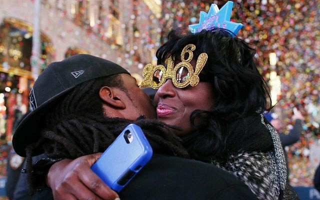 Revelers hug after the ball drops during New Year's Eve celebrations in Times Square on January 1, 2016 in New York. (AFP Photo/Kena Betancur)