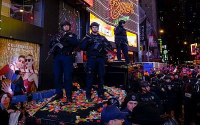 New York police officers stand guard amid airborne confetti during New Year's Eve celebrations at Times Square on January 1, 2016 in New York City. (Eduardo Munoz Alvarez/Getty Images/AFP)