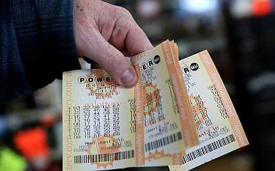 A customer holds a handful of Powerball tickets at Kavanagh Liquors on January 13, 2016 in San Lorenzo, California. (Justin Sullivan/Getty Images/AFP)