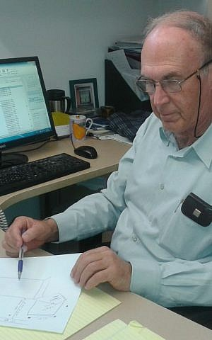 Dr. Avi Ramot, director of the Israel Center for Accessibility, reviews plans for protected bus stops. (Shekel)