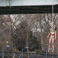 Illustrative: An activist hangs from a noose-like rope from a Paris bridge to call attention to the large number of executions in Iran,  January 28, 2016. (AP Photo/Zacharie Scheurer)