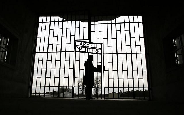 A man enters the Sachsenhausen Nazi death camp through the gate below the phrase 'Arbeit macht frei' (work sets you free) on International Holocaust Remembrance Day, Jan. 27, 2016, in Oranienburg near Berlin, Germany. (AP Photo/Markus Schreiber)