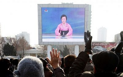 North Koreans watch a news broadcast on a video screen outside Pyongyang Railway Station in Pyongyang, North Korea, January 6, 2016. (AP/Kim Kwang Hyon)